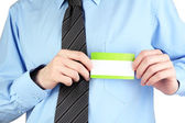 Businessman wearing blue shirt with tie and holding blank nametag close up — Stock Photo