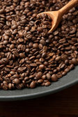 Black wok pan with coffee beans on wooden table, close up — Stock Photo