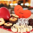 Sweet cookies with heart and valentine card on table in cafe — Stock Photo