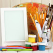 Photo frame as easel with artist's tools on wooden background — Lizenzfreies Foto