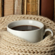 Cup of coffee wrapped in scarf on books background - Stockfoto