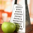 Metal grater and apple, on bright background - Stock Photo