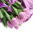 Beautiful bouquet of purple tulips on satin cloth, isolated on white — Stock Photo