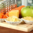 Metal grater and apple, cheese, carrot, on cutting board, on bright background — Stock Photo #21771579