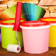 Set for painting: paint pots, paint-roller, palette of colors on stone wall background — Stock Photo #21772111
