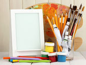 Photo frame as easel with artist's tools on wooden background — Stock Photo