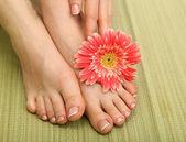Krásná žena nohy a ruce, na bambusové rohoži — Stock fotografie