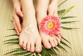 Beautiful woman legs with cream, on bamboo mat — Foto de Stock