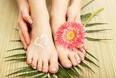 Beautiful woman legs with cream, on bamboo mat — Stock Photo
