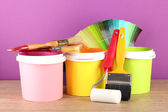 Paint pots, paintbrushes and coloured swatches on wooden table on purple background — Stock Photo