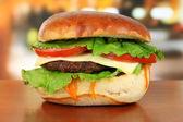 Grande y sabrosa hamburguesa en mesa de café — Foto de Stock