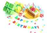 Gâteau d'anniversaire coloré avec bougie et cadeaux isolé sur blanc — Photo