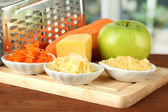 Metal grater and apple, cheese, carrot, on cutting board, on bright background — Stock Photo