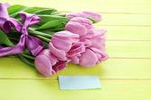 Schönen blumenstrauß von lila tulpen auf grünem holz hintergrund — Stockfoto