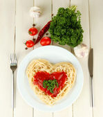 Cooked spaghetti carefully arranged in heart shape and topped with tomato sauce, on wooden background — 图库照片