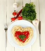 煮熟的面条仔细安排在心的形状,配以西红柿酱,木制背景上 — 图库照片