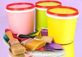 Set for painting: paint pots, brushes, palette of colors on lilac background — Stock Photo