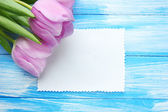 Beautiful bouquet of purple tulips and blank card on blue wooden background — Stock Photo