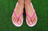 Beautiful woman legs in summer slippers on green grass — Stock Photo