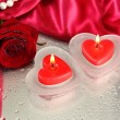 Stock Photo: Beautiful candles, rose and red silk on grey wet background