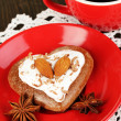 Chocolate cookie in form of heart with cup of coffee on wooden table close-up - Stock fotografie