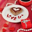Chocolate cookie in form of heart with cup of coffee on pink tablecloth close-up - Stock fotografie