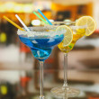 Yellow and blue cocktails in glasses on room background — Stock Photo
