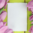 Beautiful bouquet of purple tulips and blank card on green wooden background — Stock Photo #21913491