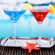 Glasses of cocktails on table near pool — ストック写真