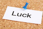 Push pin on paper with word luck on cork board — Stock Photo
