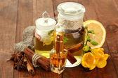 Bottiglie con ingredienti del profumo su fondo in legno — Foto Stock