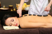 Beautiful young woman in spa salon with spa stones, on dark background — Stock Photo