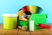 Paint pots, paintbrushes and coloured swatches on wooden table on blue background — Стоковое фото