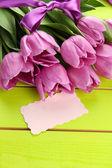 Mooi boeket van paarse tulpen op groene houten achtergrond — Stockfoto