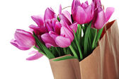 Beautiful bouquet of purple tulips in paper bag, isolated on white — Stock Photo