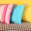 Colorful pillows on couch on yellow background — Stock Photo #21921525