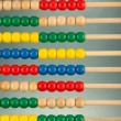 Bright wooden toy abacus, on grey background - Stock Photo