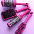 Comb brushes on purple background — Stock Photo