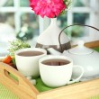 Cups of tea with flower and teapot on wooden tray on table in room — Stock Photo #21922025