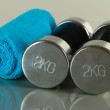 Stock Photo: Dumbbells with towel on grey background