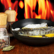 Fish in frying pan with herbs and lemon on board on wooden table on fire background — Stock Photo