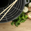 Black wok pan and vegetables on kitchen wooden table, close up - Stock Photo