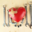 Heart and tools. Concept: Renovation of heart. On wooden background — Stock Photo