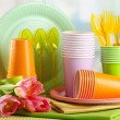 Multicolored plastic tableware on table with tulips close up — Stock Photo #21923335