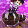 Glass bowls with coffee beans,brushes and candles on bright background — Stock Photo