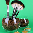 Glass bowls with coffee beans,brushes and candles on green background — Stock Photo