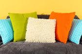 Barevné polštáře na pohovce na žlutém podkladu — Stock fotografie