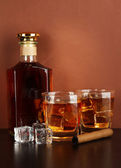 Bottle and Glasses of whiskey and cigar on brown background — Stock Photo