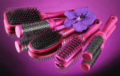 Comb brushes and flower on purple background — Zdjęcie stockowe