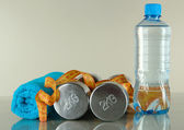 Dumbbells with towel,centimeter and bottle of water on grey background — Stock Photo